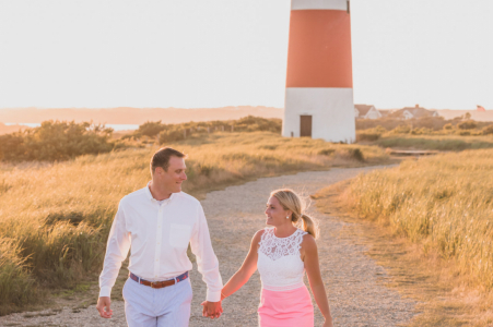 Sankaty Lighthouse environmental engagement e-session on Nantucket Island, MA of couple taking a stroll with a lighthouse behind them