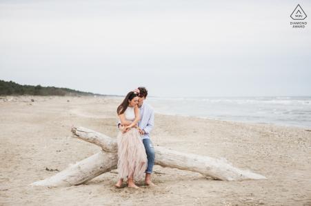 Ravenna Wild Beach portrait e-session - couple hug on a log delivered by the sea