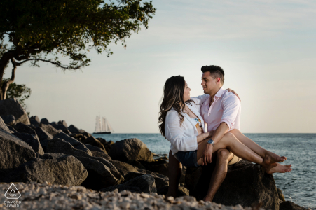 Fort Zach State Park portrait e-session with a couple sitting on rocks at the beach with a sailboat at the horizon