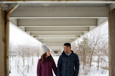 Jean-Drapeau Park, Montreal, Quebec on-location portrait e-shoot with an Engaged couple under a bridge in the winter snow