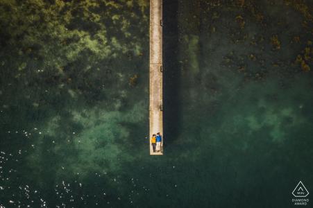 Golf du Morbihan, France Drone sur place portrait e-shoot du couple fiancé allongé sur un quai en bois au bord de l'eau