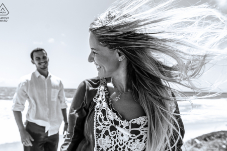 Maceió, Alagoas portrait e-session created as the woman smiles while her fiance is watching, and her hair is flying