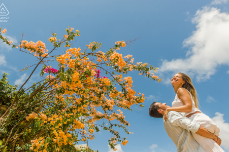 Maceió, Alagoas environmental engagement e-session with a man holding his future bride in his lap and she smiles
