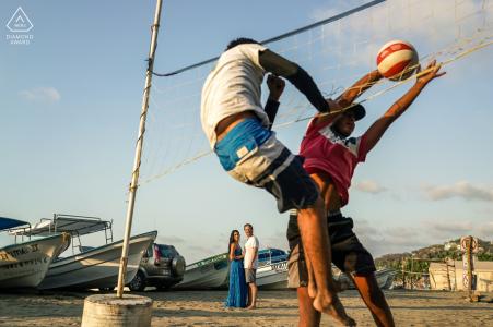 True Love Engagement Portrait Session à Sayulita, Nayarit montrant un couple sur la plage de Mexico avec des bateaux et des joueurs de volley-ball