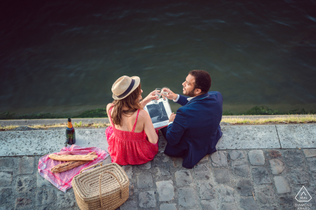 True Love Engagement Portrait Session at the River Seine in Paris displaying a couple having a picnic on The banks of the River