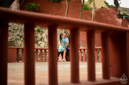 Séance de portraits de fiançailles True Love à El Chorro à San Miguel de Allende montrant un couple où des piliers rouges ont été utilisés pour encadrer le couple et la couleur rouge le rend magnifique