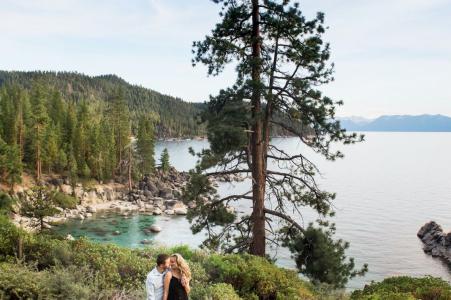 Une séance de portrait avant le mariage du Nevada True Love à Lake Tahoe montrant un couple au-dessous d'un grand pin au bord de l'eau à étreintes surplombant le lac Tahoe au coucher du soleil