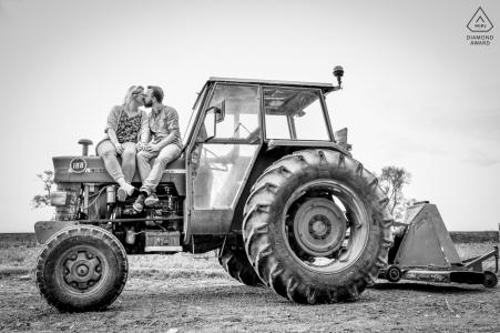 Séance photo de fiançailles True Love à la ferme familiale montrant les futurs mariés sur le tracteur familial