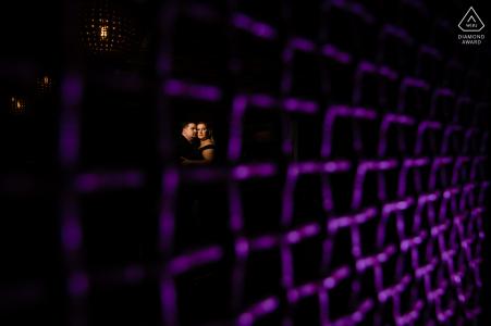Séance photo de fiançailles True Love au Sidecar New Braunfels montrant un couple derrière un filet à mailles allumé en violet