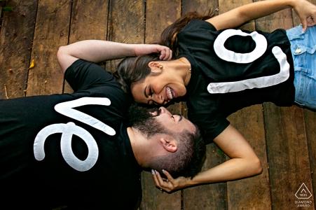 Séance de portrait avant le mariage True Love à Fazenda Água Limpa à Hidrolândia illustrant un couple allongé sur le sol en bois avec des chemises épelant LOVE