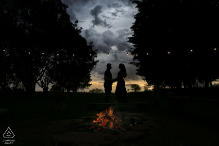 True Love Pre-Wedding Portrait Session at Fazenda Água Limpa in Hidrolândia  capturing a GO couple holding each other below the sunset clouds