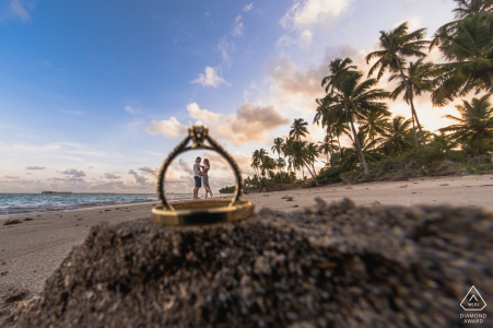 True Love Pre-Wedding Portrait Session in Maragogi illustrating a couple in front of the sea and photographed through rings in the sand