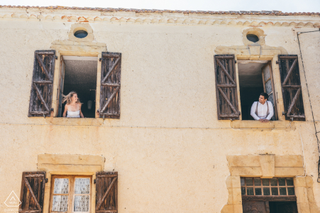 France couple e-session in Marciac showing them looking at each other in the window