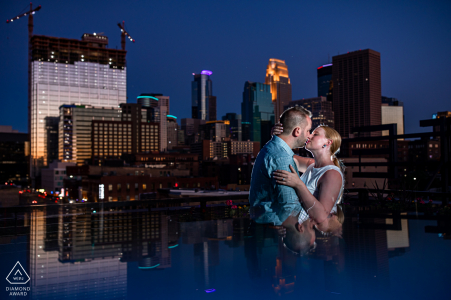 Séance électronique pour un couple de Minneapolis à l'hôtel Hewing s'embrassant avec la vue sur la ville derrière eux