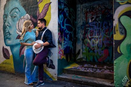 E-shoot de pareja de Knoxville en Market Square de pie junto a paredes cubiertas de hermoso arte callejero