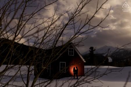 Frisco par e-session en una colina de tubos siluetas contra un granero rojo en la nieve.