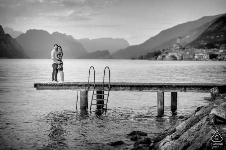 E-shoot de pareja en el lago de Garda para un retrato de compromiso en un muelle con vistas a la pequeña ciudad de Malcesine y a las montañas