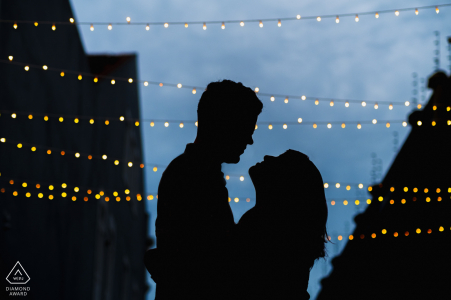 Maceió couple e-session in Silhouette with buildings and strings of lights