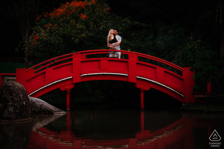 Toulouse bride and groom to be, modeling for a Jardin Japonais pre-wedding picture on a red bridge