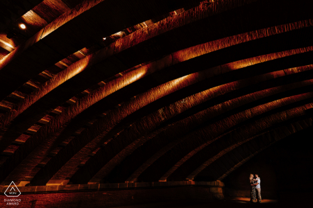 Braut und Bräutigam in Toulouse, die für ein Hochzeitsfoto vom Quai de la Daurade modeln, das die Liebe bei Nacht unter einer beleuchteten Brücke zeigt