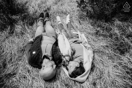 Slovenia bride and groom to be, lying in the grass for a BW engagement image at Banska Bystrica