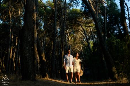 Los futuros novios de Paestum, posándose para una imagen de compromiso de bosque de pinos con una brizna de luz del atardecer