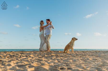 Maragogi futurs mariés, mannequin pour une photo avant le mariage alors que le couple danse sur la plage avec un chien en train de regarder