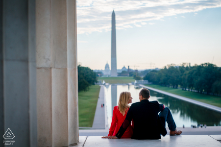 DC bride and groom to be, sitting for a Lincoln Memorial pre-wedding engagement session as the couple sit on the edge of the memorial, looking out at the reflecting pool