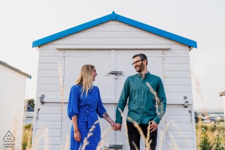 Shoreham Beach, West Sussex environmental couple pre wedding image sessionagainst an all white beach hut