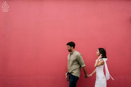 Outdoor Oaxaca City couple engagement photographie portraits de marche contre un mur peint en rouge