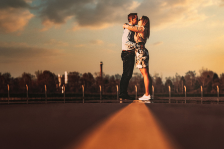 On location Szeged, Hungary couple engagement portrait shootas they Play with a line in the roadway