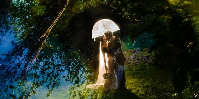 Bellas artes Retrato de novios el día de la boda en el agua con un paraguas