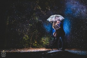 Engagement Photography of couple in the rain, lit under an umbrella | Hesse prewedding photographer
