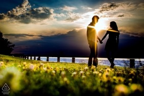 Chicago sun flares at sunset by the water for this couple holding hands during their pre-wedding shoot