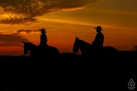 Minas Gerais engagement portraits with a couple riding horses in an orange sunset