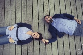 Playful portrait of a couple lying on their backs on the wood deck by a La Spezia Engagement Photographer