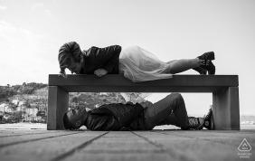 Liguria Fotograf zaręczynowy. Zabawny czarno-biały portret pary niemądrej z ławką w parku.