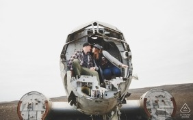 Engagement Portrait of a couple in the nose section of a downed airplane in the open field by a Stockholm wedding photographer