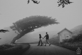 California Engagement Photo. They cross the road hand in hand in this foggy black-and-white portrait.