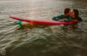 Biscay surfing couple engagement shoot | wet suits and a surfboard suit these newlyweds in the water very well