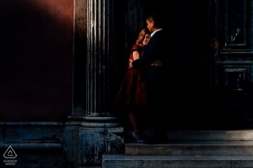 a shaft of soft light illuminates this Rome couple during a portrait shoot next to a city column