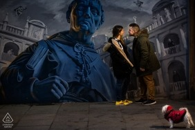Spain Engagement Photographer. Street art wall mural portrait with a small dog in a red jacket.