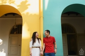 Colorful Singapore Engagement Portrait of a couple against painted arching walls.