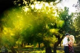 Sesja zaręczynowa na świeżym powietrzu w Trapani pośród wysokich zielonych drzew i słońca