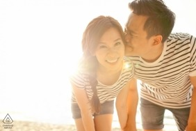 Malacca Malaysia engagement session - pre-wedding portraits with a couple wearing matching striped outfits at the beach