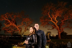 CA lit engagement portrait at dusk with two big trees.