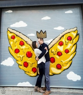 Pizza angel wings and I crown for her fiancé against a metal rollup door in Madison Wisconsin - engagement and wedding photography