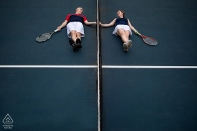 Washington DC, match game - tennis loving couple lie on the court holding hands through the net during their pre-wedding portrait
