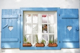 Window in the village with planter boxes and shutters framed this Romanian couple for their engagement portrait