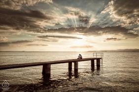 Para Perugia siedzi na molo / przystani na plaży, gdy zachodzi słońce